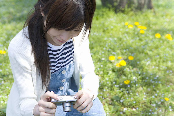 Woman Smiling And Holding A Digital Camera On Lawn, Front View, Japan Photograph by Daj