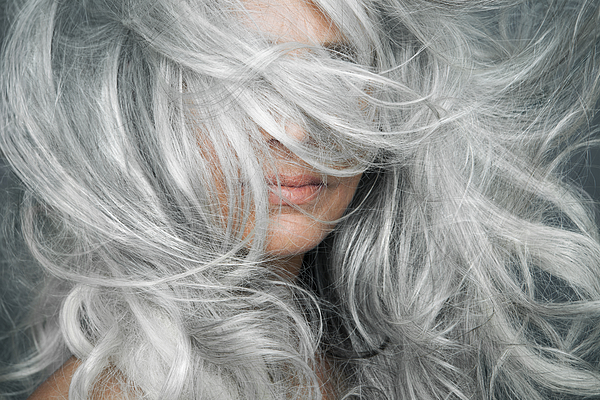 Woman With Grey Hair Blowing Across Her Face. Photograph by Andreas Kuehn