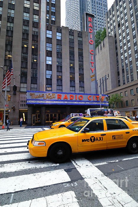 Building Photograph - Yellow Cabs Pass In Front Of Radio City Music Hall by Amy Cicconi