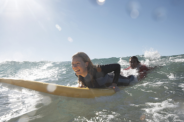Young Man Being Towed In Sea By Young Woman On Surfboard, Smiling Photograph by Anthony Ong
