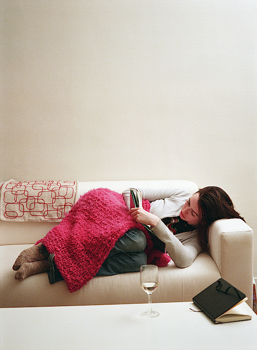 Young Woman Lying On Couch, Reading Book Photograph by Robert Warren