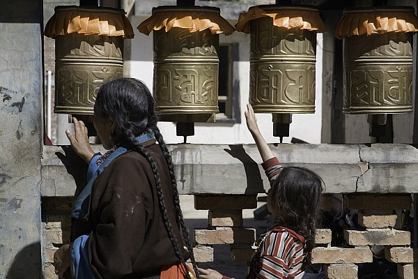 Qinghai Province Photograph - A Buddhist Woman And Child Spin Brass by David Evans