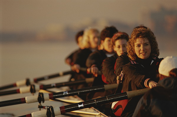 Sports Photograph - A Crew Team Paddles In Unison by Sam Kittner