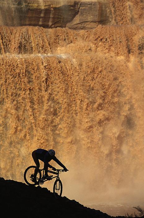 Water Photograph - A Mountain Biker Pedals Past Rushing by Bill Hatcher
