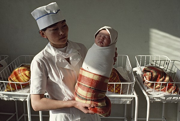 Two People Photograph - A Nurse Holds A Tightly Wrapped Newborn by Dean Conger