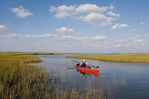 Outdoors Photograph - A Sea Kayaker And Fisherman Paddles by Skip Brown