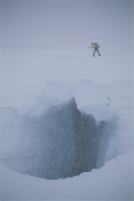 Sports Photograph - A Skier Above A Deep Glacier Crevasse by John Burcham