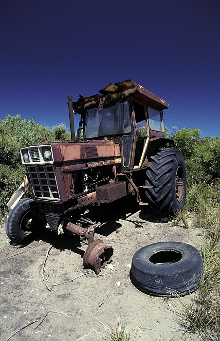 Abandoned Photograph - An Abandoned Tractor Rusts Away by Jason Edwards