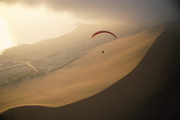 South America Photograph - Ocean Gusts Keep A Paraglider Aloft by Joel Sartore
