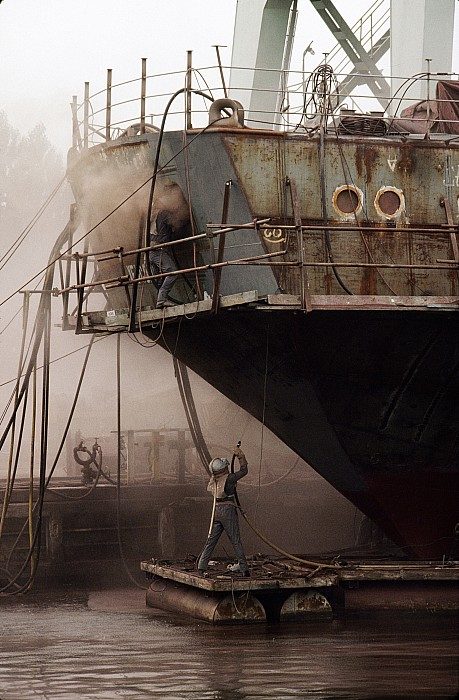 Outdoor Photograph - Sandblasters Restore A Soviet Ship by Cotton Coulson