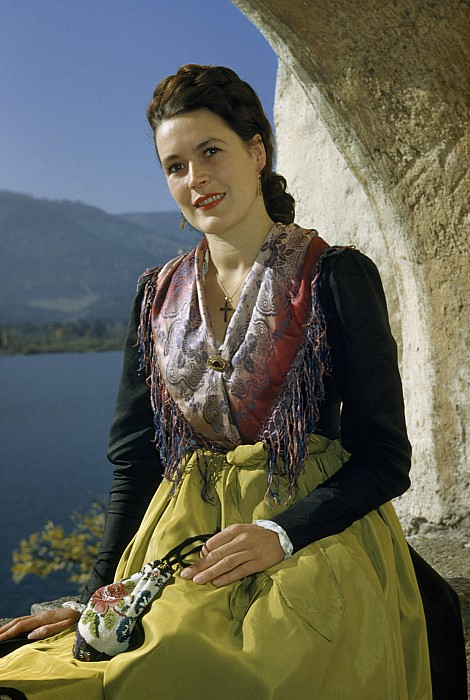 Outdoors Photograph - Seated Woman Wears Dirndl Skirt by Volkmar Wentzel