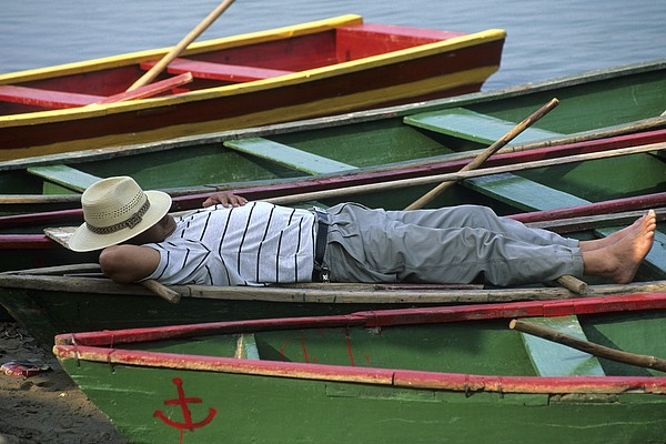 Outdoors Photograph - Tour Boat Guide Naps Amidst Rowboats by Raymond Gehman