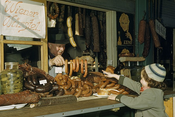 Outdoors Photograph - Vendor Holds Up Sausages For Young Girl by Volkmar Wentzel