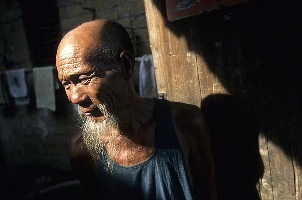 Outdoors Photograph - Village Elder At Doorway, Yangdi by Raymond Gehman