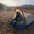 A Camper Reading In Her Tent by Gordon Wiltsie
