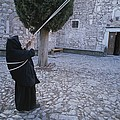 A Nun Pulls On Ropes In A Courtyard by Tino Soriano