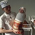 A Nurse Holds A Tightly Wrapped Newborn by Dean Conger