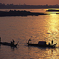 Boats Silhouetted On The Mekong River by Steve Raymer