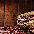 Burlap Sack Of Coffee Beans Against Dark Wood by Sandra Cunningham