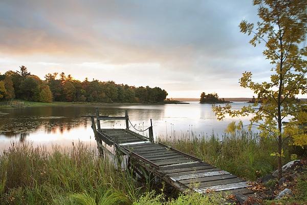 Sunrise Photograph - A Dock On A Lake At Sunrise Near Wawa by Susan Dykstra