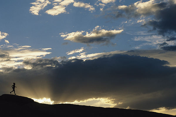 Sky Photograph - A Silhouetted Figure Trail Running by Bobby Model