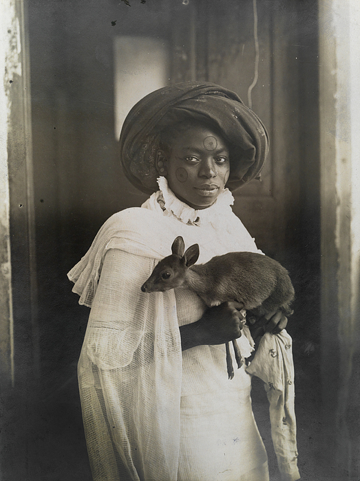 Black And White Photograph - A Young Kenyan Woman Holds Her Pet Deer by Underwood And Underwood