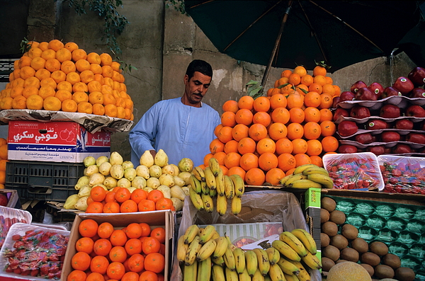 Abundance Photograph - Market Vendor Selling Fruit In A Bazaar by Sami Sarkis