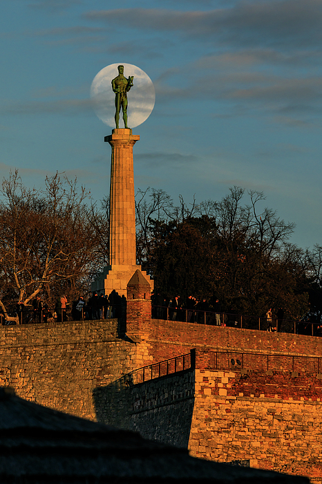 Moon Photograph - The Moon Rising Behind The Victor Statue In Belgrade In The Golden Hour by Dejan Kostic