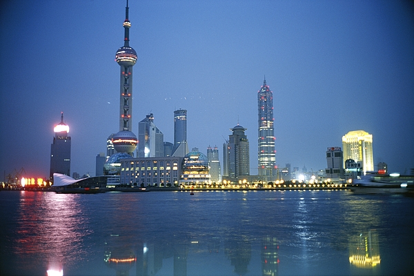Cityscapes Photograph - The Shanghai Skyline And Riverfront by Raul Touzon
