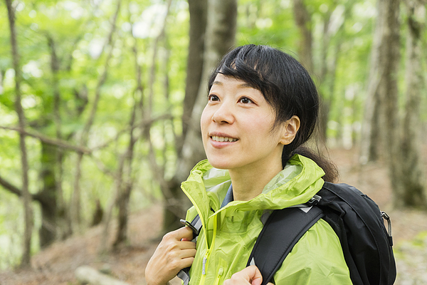 Asian woman hiker walking on trail in nature. Photograph by Yagi-Studio