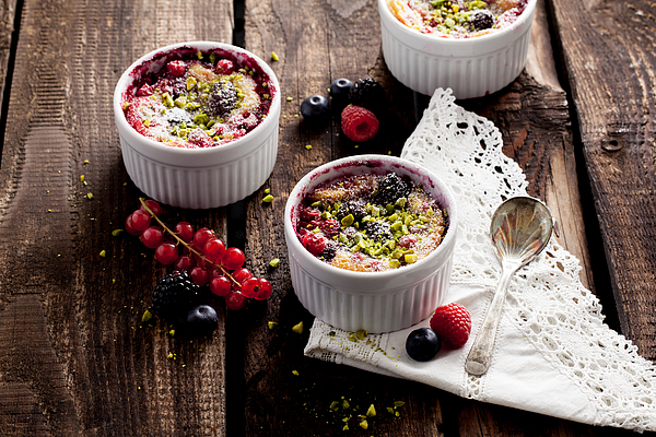 Berries soufflé on wooden board served as dessert Photograph by Carolafink