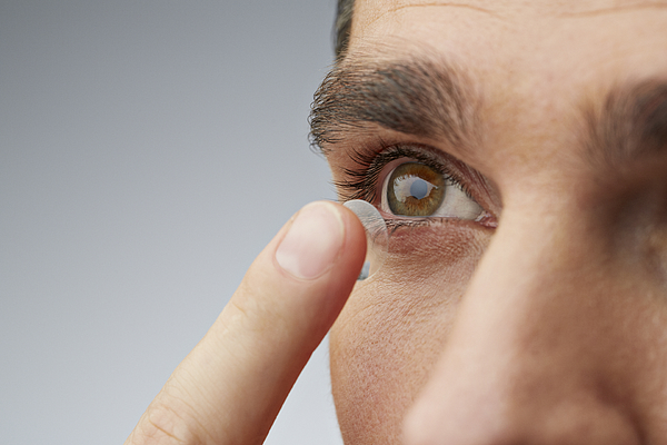 Close up of man putting in contact lens Photograph by Klaus Vedfelt
