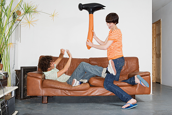 Couple playing with inflatable hammer Photograph by Image Source