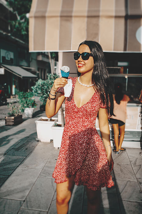 Fashionable Young Woman Eating Ice Cream In The City Photograph by Carol Yepes