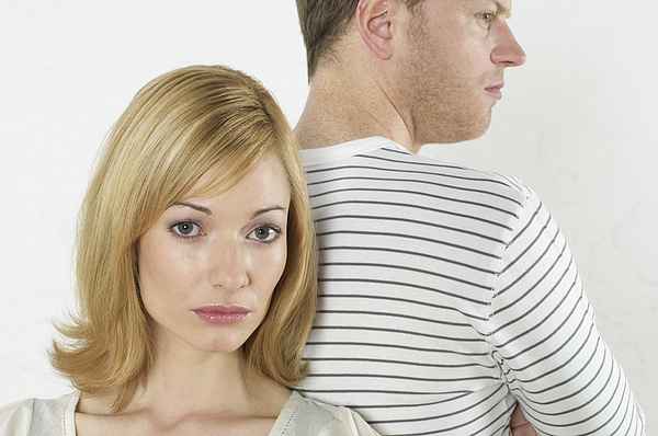 Frustrated couple standing back to back Photograph by Stock4b-rf