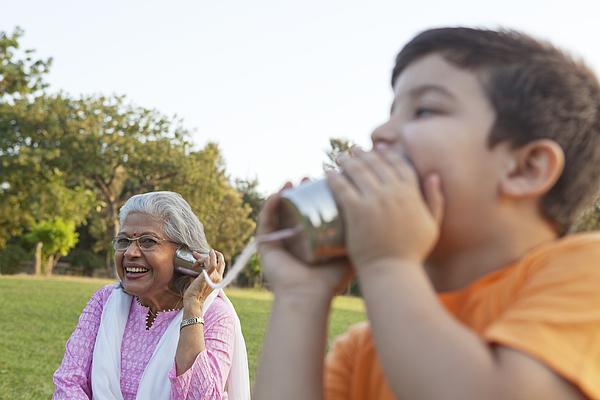Grandmother and grandson talking through tin cans Photograph by Ravi Ranjan