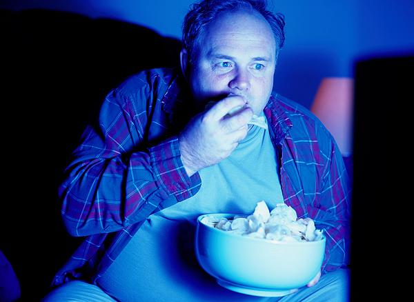 Man Eating Potato Chips and Watching Television Photograph by Ryan McVay