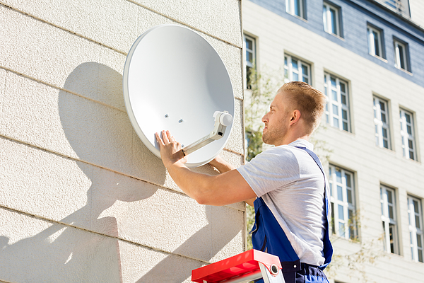 Man Fitting TV Satellite Dish Photograph by AndreyPopov