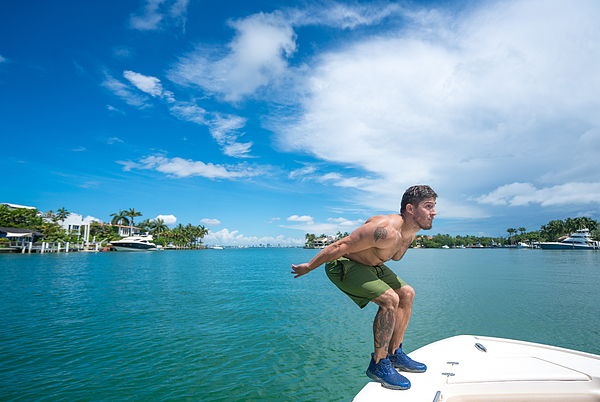 Man jumping off boat Photograph by Thepalmer
