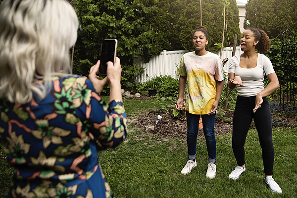 Mixed-race sisters being filmed by mother in backyard. Photograph by Martinedoucet