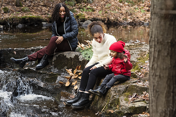 Mixed-race sisters relaxing on river side in autumn nature. Photograph by Martinedoucet
