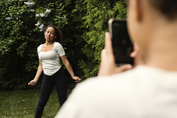 Mixed-race teenage sisters filming with mobile phone in backyard. Photograph by Martinedoucet
