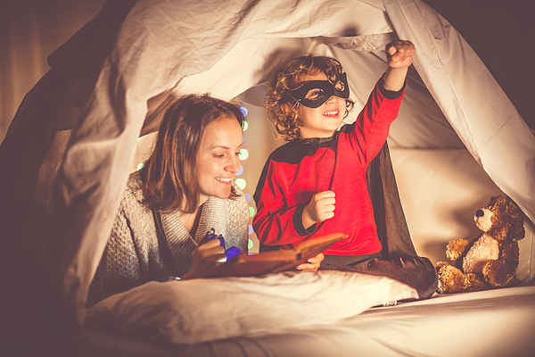 Mother reading a story to her son at bedtime Photograph by Kontrec