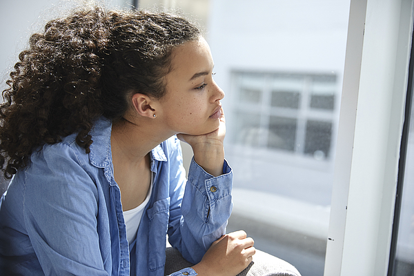 Sad and unhappy teenager looking out of the window Photograph by Anna Frank