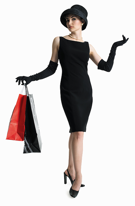 Silhouette Of Attractive Sophisticated Caucasian Woman In Black Dress Hat As She Holds Shopping Bags Photograph by Photodisc