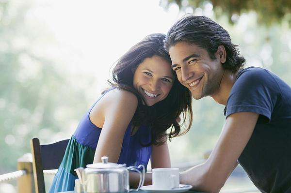 Smiling couple having tea outdoors Photograph by Tom Merton