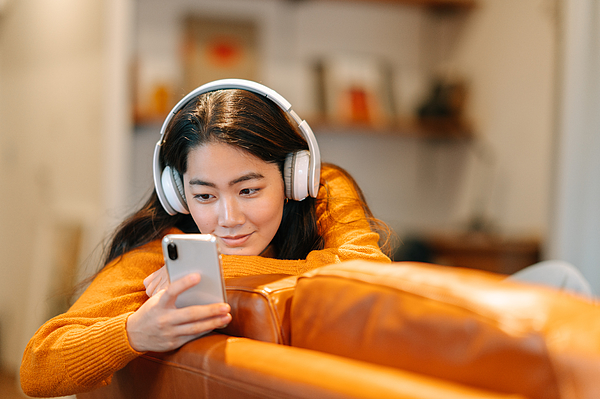 Stylish young woman listening to music at home Photograph by Recep-bg