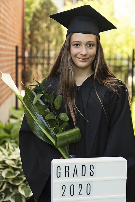 Teenage girl graduation from primary school portrait in backyard. Photograph by Martinedoucet
