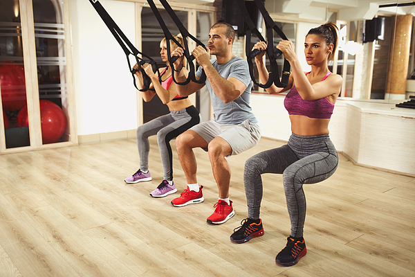 TRX suspension training- people doing arm and leg exercises Photograph by EmirMemedovski