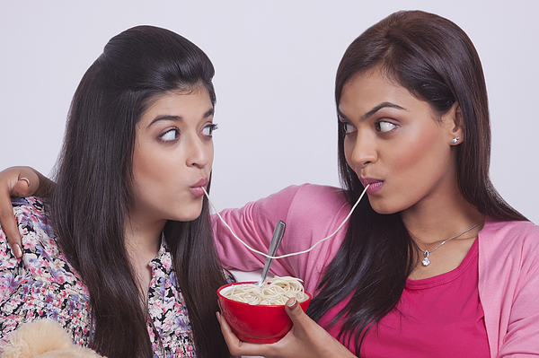 Two young women eating noodles Photograph by Sudipta Halder